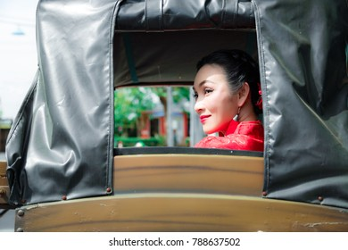 Portrait charming beautiful Chinese woman: Attractive middle aged women is sitting on chinese rickshaw. Gorgeous asian woman wears chinese dress. Female feels happy and relaxed. Lady has nice smile