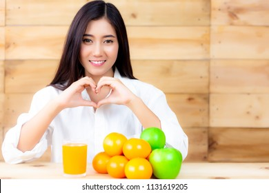 Portrait charming beautiful healthy woman. Attractive beautiful woman is making symbol of love for telling someone who take care their self well by eating fruits, they will get good health. copy space