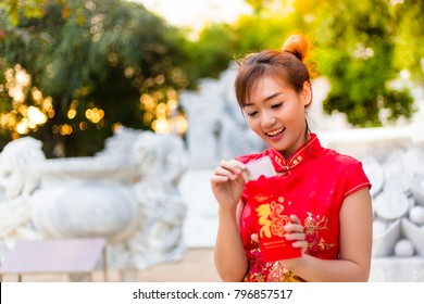 Portrait charming beautiful lucky chinese woman: Attractive woman gets some money with red envelope that means happy lucky and wealthy. Charming chinese female is surprising when she open the envelope