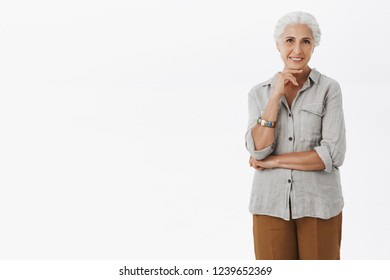 Portrait of charming beautiful old woman with grey combed hair holding hand on chin and gazing interested at camera hearing curious and intriguing promotion deciding how invest money