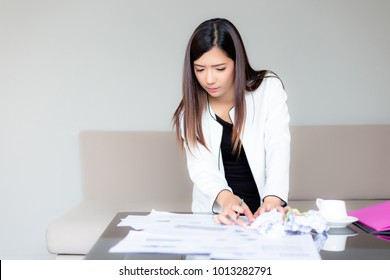 Portrait charming beautiful professional businesswoman: Attractive woman is working on messy desk. Gorgeous girl look so busy. She feel unhappy and confused of her work. Asian female get stressed.
