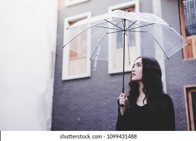 Portrait charming beautiful woman. Attractive beautiful woman is looking at sky. Gorgeous girl holds umbrella because it's nearly raining. Glamour lady is walking around the city or town. copy space