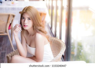 Portrait charming beautiful woman. Attractive beautiful women is sitting on chair at restaurant. Gorgeous girl looks sexy and happiness. Pretty girl has blond hair. She has nice skin and looks healthy