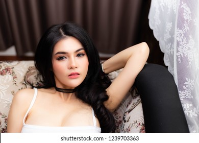 Portrait charming beautiful woman. Attractive beautiful girl is laying down on sofa near window at her house. Sexy woman feels relaxing and comfortable in summer season. Pretty woman wear camisole.