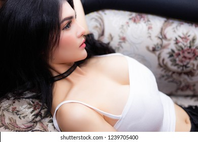 Portrait charming beautiful woman. Attractive beautiful woman is thinking something and laying down on sofa at home Sexy woman wear camisole. She has nice skin and perfect body. She has beautiful face