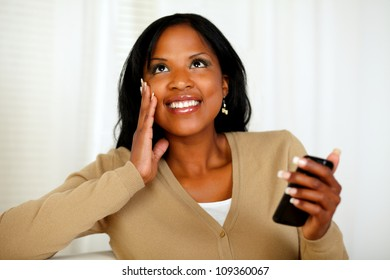 Portrait of a charming black woman holding a mobile phone while is looking up