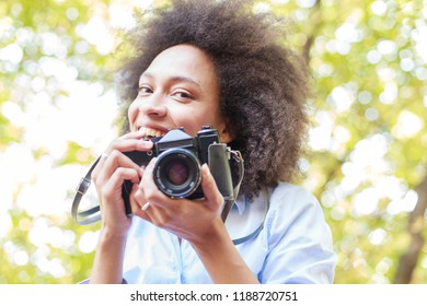 Portrait of charming black woman with old retro camera, female photographer outdoor, afro hairstyle, wears casual clothes , looking at camera