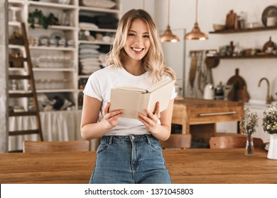 Portrait of charming blond woman 20s wearing casual t-shirt reading book while standing in stylish wooden kitchen at home