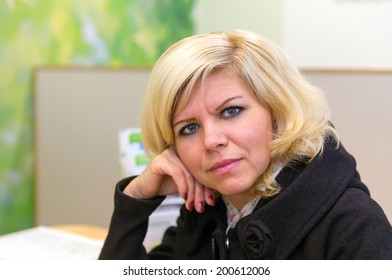 Portrait of charming blonde in a black coat
