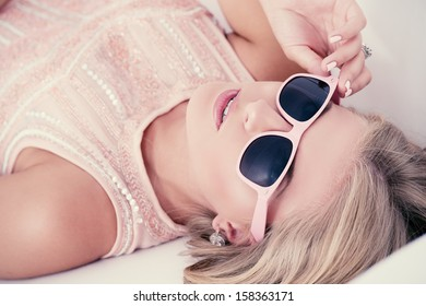 Portrait of a charming blonde girl in pink sunglasses.