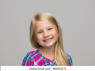 Portrait of a charming blonde little girl, isolated on gray background