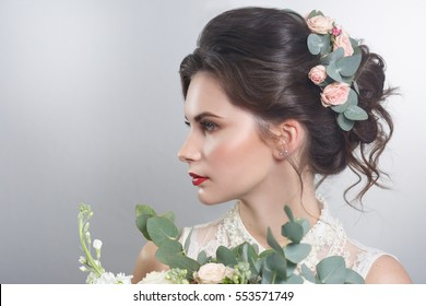 Portrait of charming bride with a bouquet in his hands in profile isolated on a gray background.