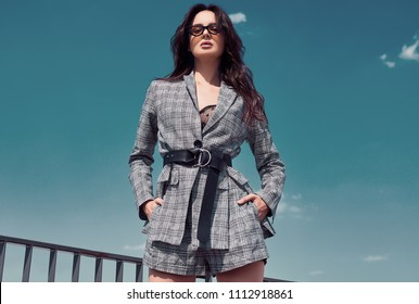Portrait of a charming bright brunette woman wearing woolen checkered business suit posing on the roof of a building