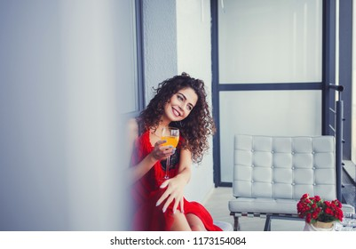 portrait of charming brunette woman with perfect smile and holding glass of juice