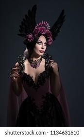 Portrait of charming brunette woman in rose crown posing on dark background