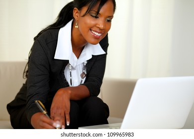 Portrait of a charming businesswoman on black suit working while sitting on couch in front of her laptop