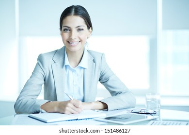 Portrait of a charming businesswoman sitting at her workplace and writing