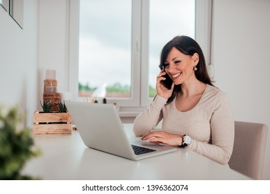 Portrait of a charming casual woman sitting at desk with laptop and talking on smarphone.