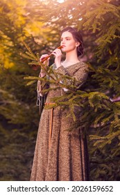 Portrait of Charming Caucasian Brunette Female in Old Medieval Green Dress With Flute Against Firtrees Outdoors.Vertical Image Composition