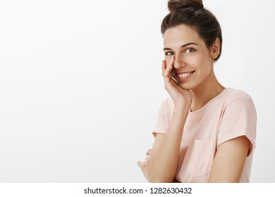 Portrait of charming charismatic european woman with combed hair standing right side of copy space touching face as giggling flirty and smiling sincere at camera giving warm sweet gaze