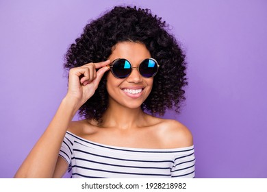 Portrait of charming cheerful dark skin girl hand touch sunglass beaming smile isolated on purple color background
