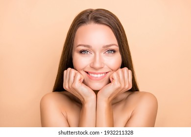 Portrait of charming cheerful girl enjoying pure natural skin hydration isolated over beige pastel color background