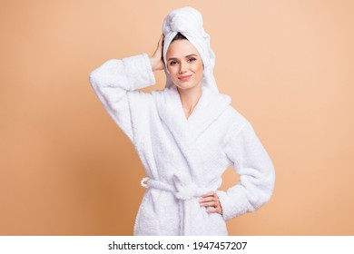 Portrait of charming cheerful girl wearing white bathrobe enjoying relax isolated over beige pastel color background