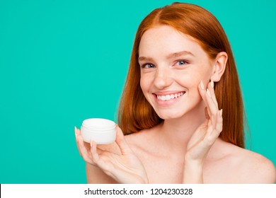 Portrait of charming cheerful nude red-haired girl with shiny pure clean fresh smooth flawless skin, testing daily cream from jar, isolated over green turquoise background