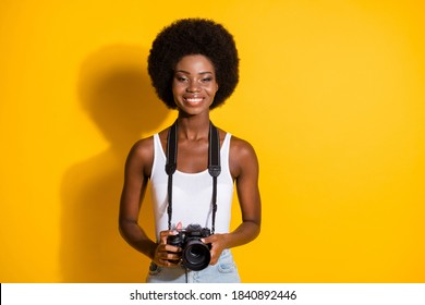 Portrait of charming cheerful thin wavy-haired girl holding in hands digicam cam isolated over bright yellow color background
