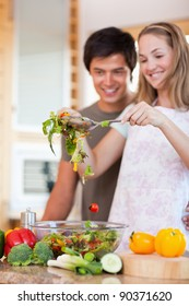 Portrait of a charming couple making a salad in their kitchen