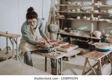 Portrait of charming craftswoman sitting on bench while kneading and shaping clay in pottery workshop. She looking down with serious expression