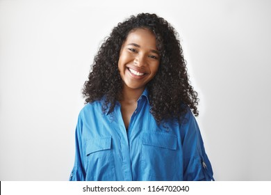 Portrait of charming cute young African woman with smooth brown skin and curly healthy hair posing at white wall, looking at camera and smiling broadly, showing white teeth. Toothpaste and haircare