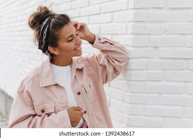 Portrait of charming dark-haired woman in pink jacket leaned on light brick wall