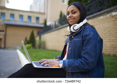 Portrait of charming dark-skinned student in jeans jacket chatting in social networks sitting on campus with laptop, positive afro american hipster girl blogging on personal website enjoying leisure