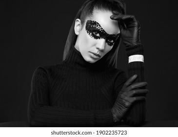 Portrait of charming elegant brunette woman in turtleneck sweater and sequins mask posing on black background in studio