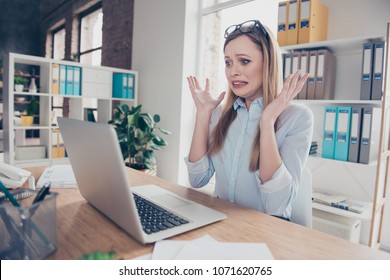 Portrait of charming, emotional, worried, nervous woman with glasses on head and hairstyle gesture with hands, looking at computer, something went wrong, can't get in time, sitting at desk