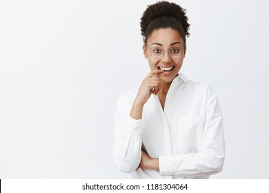 Portrait of charming emotive and feminine dark-skinned female tutor in white-collar shirt and glasses, biting finger from curiosity and smiling broadly, gazing at camera intrigued and interested