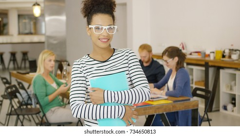 Portrait of charming ethnic woman wearing casual outfit holding notepad and smiling at camera with other workers on background in office.