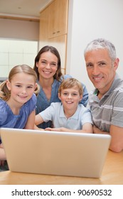 Portrait of a charming family using a laptop in their kitchen