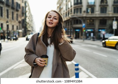 Portrait of charming female with take away coffee in hand standing on urban background. Beautiful young woman in a good mood dressed in stylish coat looking at camera enjoying city walk.