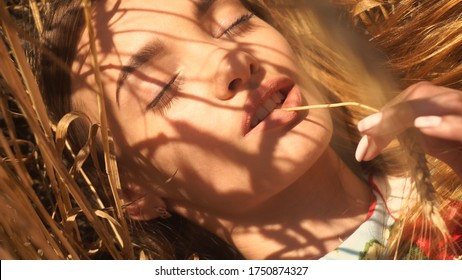 portrait charming girl lies in a field of wheat