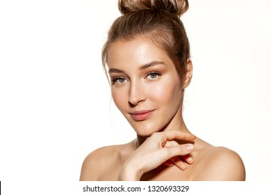 Portrait of charming girl with shiny perfectly clean skin posing for picture in studio. Natural beauty concept. Lovely model with bare shoulders on white background