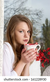 Portrait of charming girl in sweater holding cup and looking through window