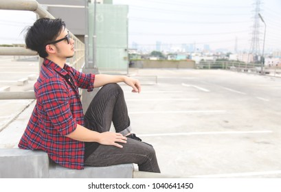 Portrait charming handsome worker guy: Attractive man looks tried and stress. Asian guy is thinking about his life. Asia man sits on  steps. He wears sunglasses, shirt, jeans. Cool man look depressed