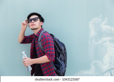 Portrait charming handsome young guy: Attractive handsome man is looking sky. Cool man walk or travel to city. Traveler man wear sunglasses and bag pack. Backpacker guy holds a bottle water copy space