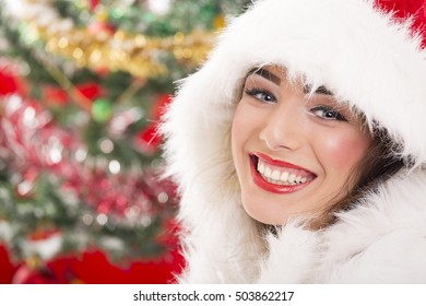 Portrait of charming happy young woman in Santa Claus costume laughing happily over blurred Christmas background.