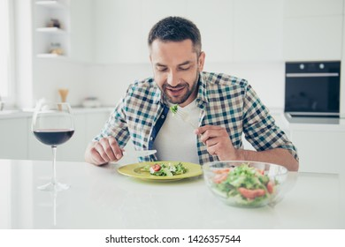 Portrait of charming imposing man hold hand silverware knife fork sit table enjoy meal morning breakfast checkered shirt clothes big light appartment room wineglass