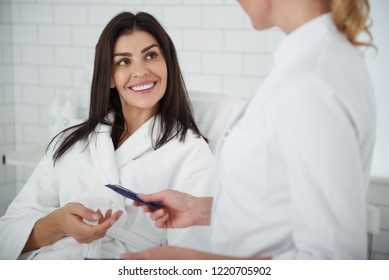 Portrait of charming lady in white bathrobe lying on daybed and looking at beautician with smile while she recommending effective skin care product