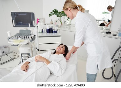 Portrait of charming lady in white bathrobe lying on daybed while beautician touching towel under her head