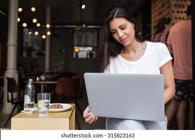 Portrait of a charming latin woman having video conference on her net-book during lunch break in modern coffee shop,young female designer using laptop computer for distance work while sitting in cafe